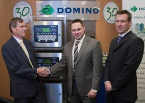 Prism managing director David Aspinall (left), Domino operations purchasing manager Ian Whitehead (centre) and Domino commodity buyer Rob Ellinor (right) pictured with Domino's best selling A400 ink jet printer.
